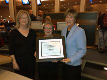 Debi and Beth accepting the Community Arts Award from Mae Rowe at the CBRM December